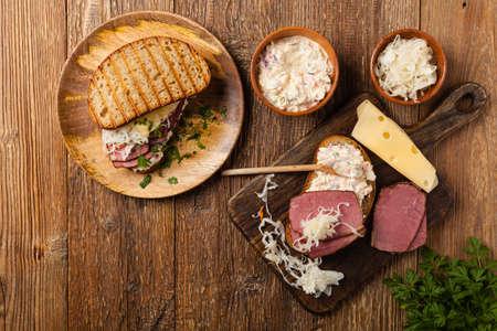 Ruben sandwich. New York sandwich with pastrami, sauce 1000 islands and sauerkraut. Top view. Fast food. Stock Photo