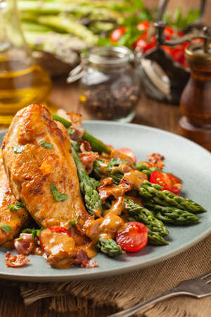 Roasted chicken breast, served on asparagus with tomato sauce, dried tomatoes. Front view. Фото со стока