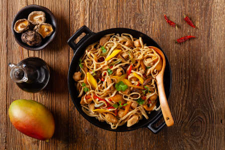 Fried chicken with mango and coconut milk with noodles. Prepared in a wok. Top view.  Фото со стока
