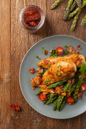 Roasted chicken breast, served on asparagus with tomato sauce, dried tomatoes. Top view.