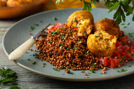 Lentil and millet meatballs. Served on tomato salsa with buckwheat. Gray plate, wooden boards in the background. Front view. Stockfoto