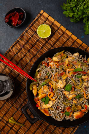 Wheat noodles with black sesame, fried in a wok with chicken and vegetables. Top view. Фото со стока