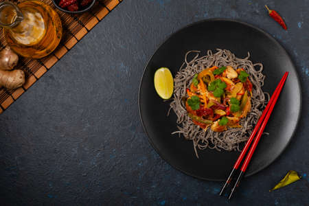 Wheat noodles with black sesame, fried in a wok with chicken and vegetables. Top view. Served on a black plate.