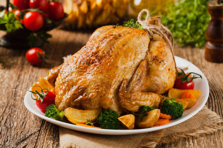 Roast chicken whole. Served on a plate with vegetables and baked potatoes. Front view. Standard-Bild