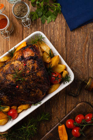 Roasted whole shoulder, with potatoes, peppers and tomatoes. Marinated in white wine.Top view. Natural wooden background. Zdjęcie Seryjne
