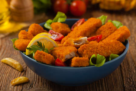 Fish sticks with salad in blue bowl. Front view.