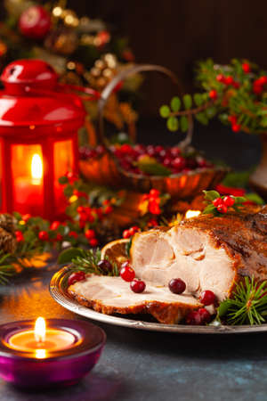 Roast pork neck in Christmas style. Dark navy blue background. Christmas accessories. Candles and lanterns in the background.
