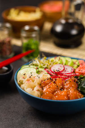 Hawaiian salmon poke bowl with seaweed, avocado, sesame seeds. Front view. Black background.