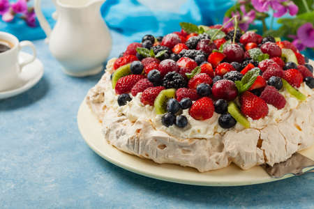 Meringue Pavlova cake with fresh fruit. Front view.