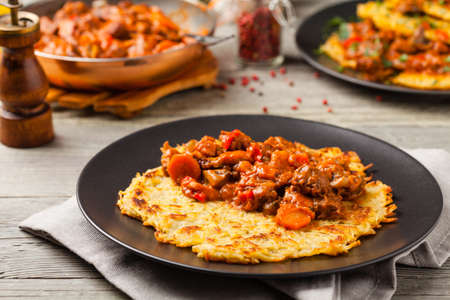Hungarian potato pancake with goulash. Front view.