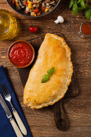 Italian calzone with mushrooms and ham. Top view.  스톡 콘텐츠