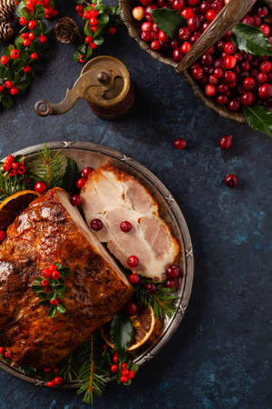 Roast pork neck in Christmas style. Dark navy blue background. Christmas accessories. Top view.