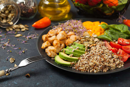 Salad with quinoa, avocado and chicken. Front view. Served on a black plate.