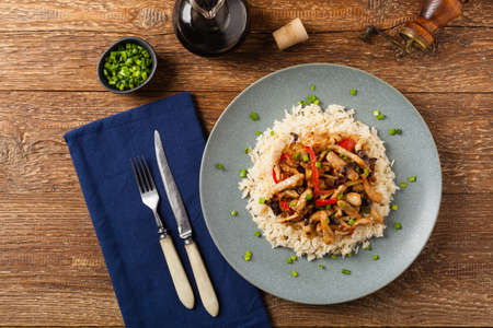 Pork chop with peppers, mushrooms and bamboo. Served with rice. Top down.