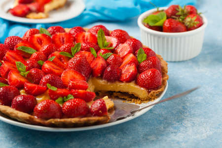 Delicious tart with strawberries on a blue painted background. Front view. Stock Photo