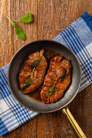 Saltimbocca. Veal schnitzel with sage and Parma ham. Italian specialty. Top view.