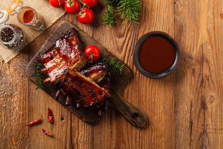 Roasted pork ribs in a bbq sauce. Served on a wooden board. Top view. Фото со стока