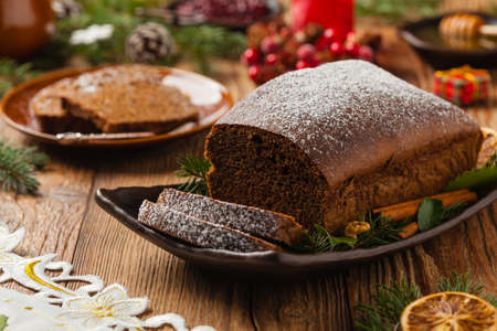 Homemade gingerbread cake. Christmas decoration. Front view. Natural wooden background.