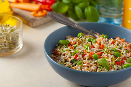 Trendy lunch with rice and vegetables. Served in a blue bowl, on a bright painted background. Front view.