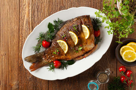 Fried carp whole. Served with lemon and cherry tomatoes on white plate. Christmas decoration. Top view.