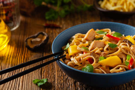 Fried chicken with mango and coconut milk with noodles. Prepared in a wok. Front view. Served in a blue bowl. 版權商用圖片