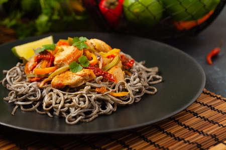 Wheat noodles with black sesame, fried in a wok with chicken and vegetables. Front view. Served on a black plate.
