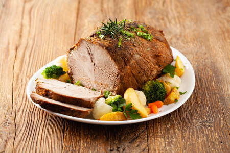 Whole cooked pork neck. Served on a white plate with vegetables and baked potatoes. 版權商用圖片