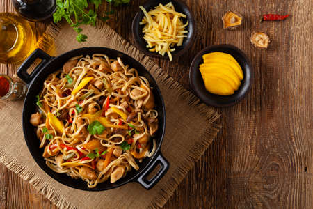 Fried chicken with mango and coconut milk with noodles. Prepared in a wok. Top view.