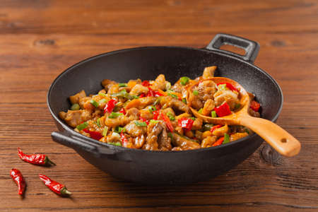 Chicken kung pao. Fried chicken pieces with peanuts and peppers. Front view. 版權商用圖片