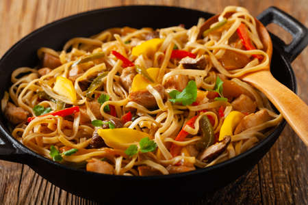 Fried chicken with mango and coconut milk with noodles. Prepared in a wok. Front view.