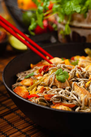 Wheat noodles with black sesame, fried in a wok with chicken and vegetables. Front view.