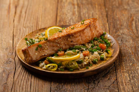 Asian dish. Fried salmon with rice and vegetables. Sprinkled with sesame seeds. Front view. Natural background.