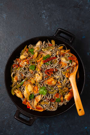 Wheat noodles with black sesame, fried in a wok with chicken and vegetables. Top view. 版權商用圖片