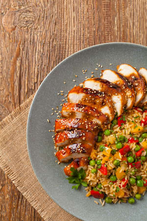 Grilled chicken breast in teriyaki sauce. Served with brown rice and vegetables. Top view. Flat lay.