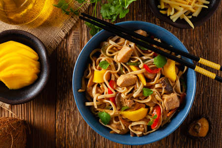 Fried chicken with mango and coconut milk with noodles. Prepared in a wok. Top view. Served in a blue bowl.