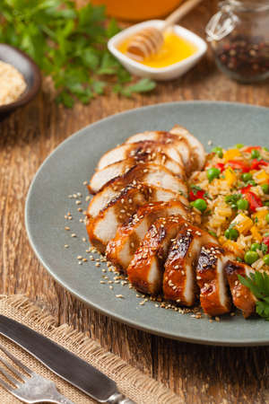 Grilled chicken breast in teriyaki sauce. Served with brown rice and vegetables. Front view.