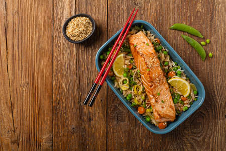 Asian dish. Fried salmon with rice and vegetables. Sprinkled with sesame seeds. Top view. Natural background.