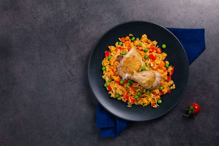 Arroz con pollo. Baked pieces of chicken with bone, rice with paprika and peas. Black background. Served on black plate or spanish pan.