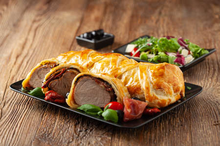Baked sirloin in puff pastry. Sliced pieces, served with sun-dried tomatoes, salad, and olives. 版權商用圖片