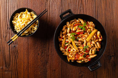 Traditional noodles with shimeji mushrooms and chicken. Prepared in a wok. Wooden background. Top view.