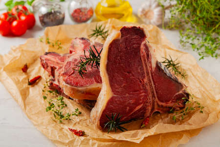 Raw t bone steak, served on paper. Herbs, stone background.