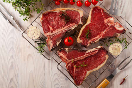 Raw t bone steak, with herbs. Grill accessories. Ready for grilling. Wooden bright background.