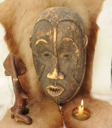wooden figure: African Mask and Praying Wooden Figure on  Natural Animal Fur.