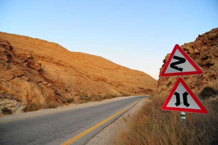 Signo de carretera de curvas peligrosas en el camino abandonado. Puesta de sol.  Foto de archivo - 5686937