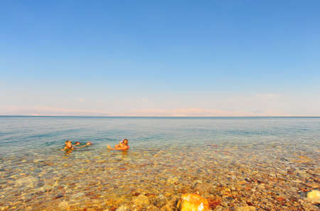 Woman And Boy Relaxing In Dead Sea Laying On Water Surface photo