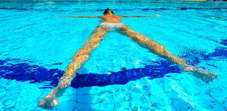 Woman Relaxing In Pool Laying On Water Surface photo