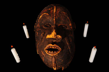 Burning Candles around the Old Wooden African Mask on Black Background