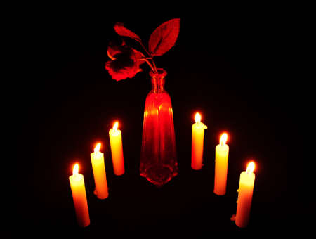 Rose in a Red Vase, Surrounded by Burning Candles on a Black Background photo