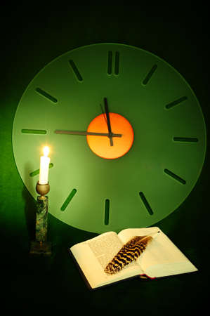 Still Life with a Clock, an Open Bible and a Lighted Candle on the Green Velvet photo