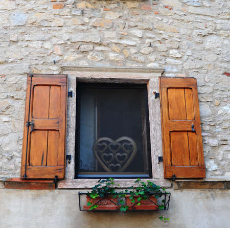 Typical Italian Window With Open Wooden Shutters, Decorated With Fresh Flowers photo